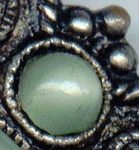 1940s? brooch with green satin glass cabochons: detail of small cabochon and metal frame detail